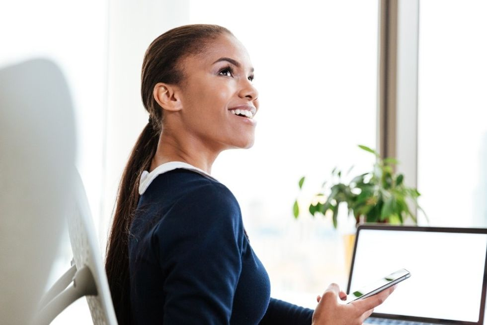 Young professional woman working at computer and happy at work because she loves her career.