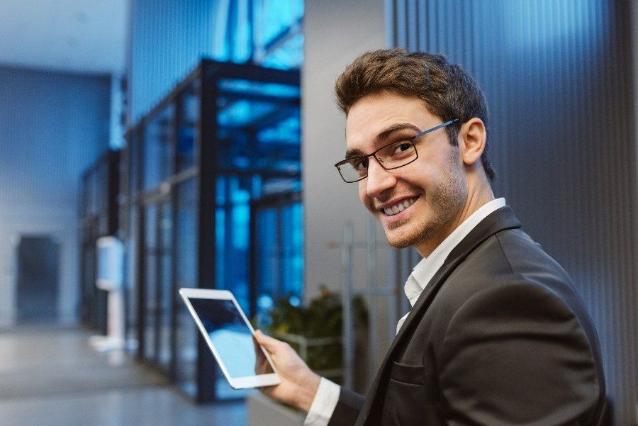 Young professional man smiling more at work and becoming happier in the workplace.