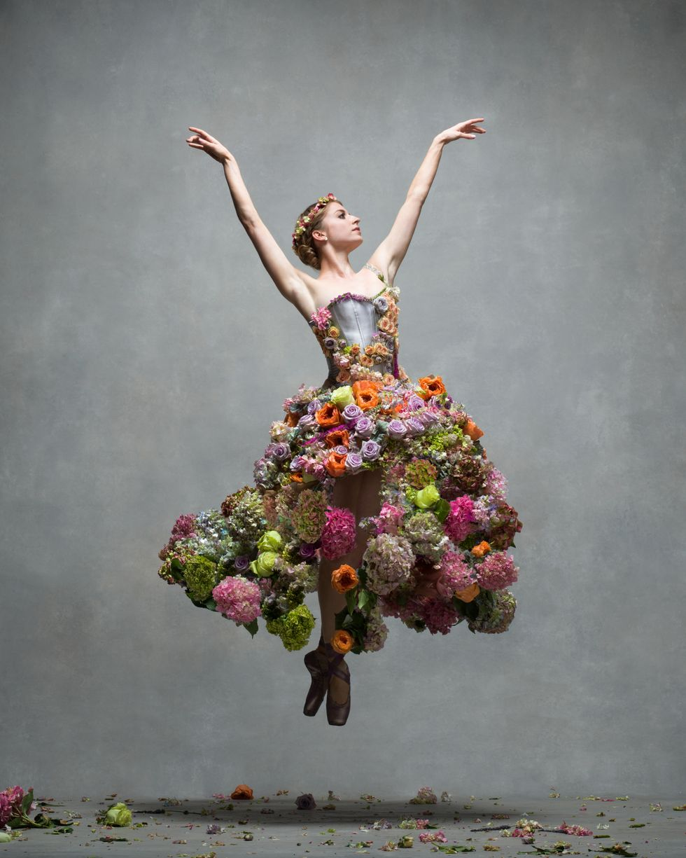 A female dancer jumps off the ground with two pointed feet and arms high over her head. Her dress has a colorful skirt made from real flowers, and there are flowers strewn on the ground.