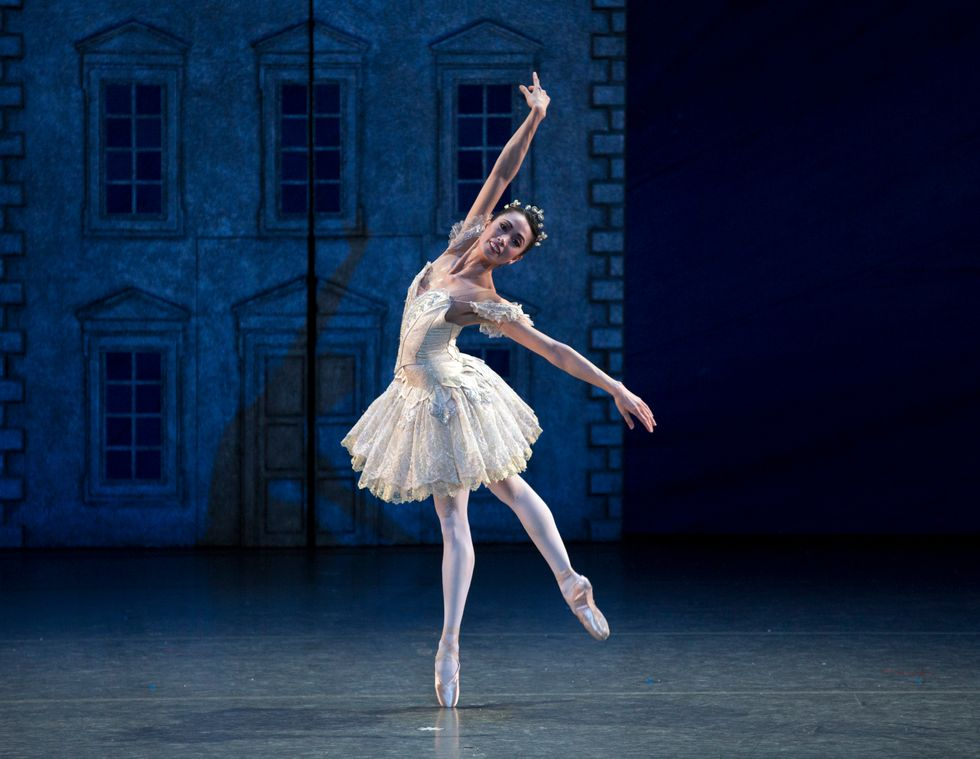 A female dancer stands onstage, balancing on one leg with her other leg raised behind her. She is wearing a white tutu and crown.