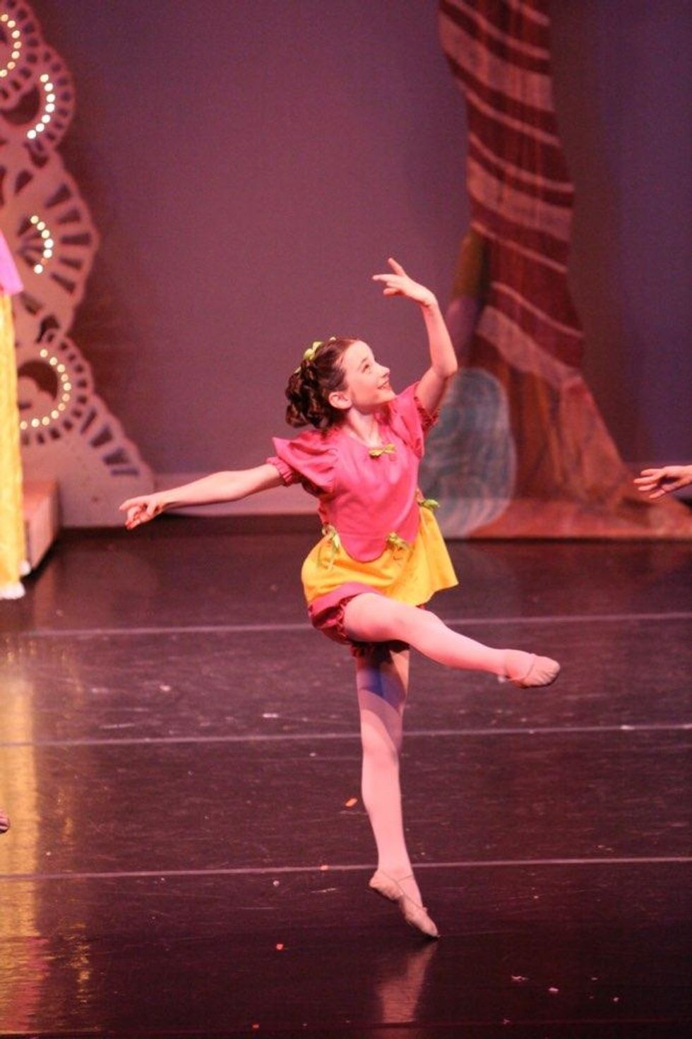 A young girl jumps lightly off one leg during an onstage performance, wearing a bright pink and yellow costume and tights.
