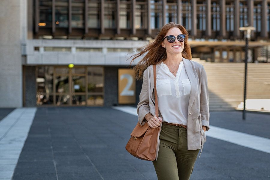 Smiling young female worker walking into work on her first day at a new office.