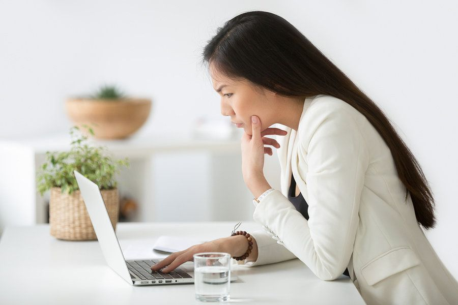 Young professional woman researching a company to determine if she should turn down a job offer.
