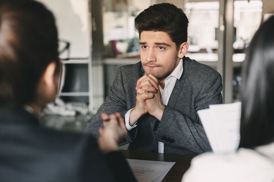 Young professional man debating whether or not he should turn down a job offer during a job interview.