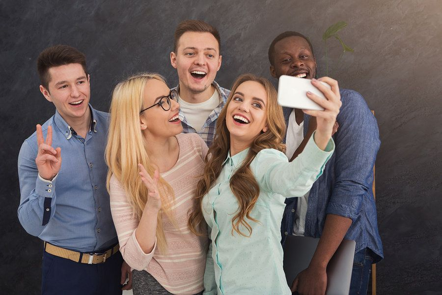 Co-workers keep things light in the office and take a selfie.
