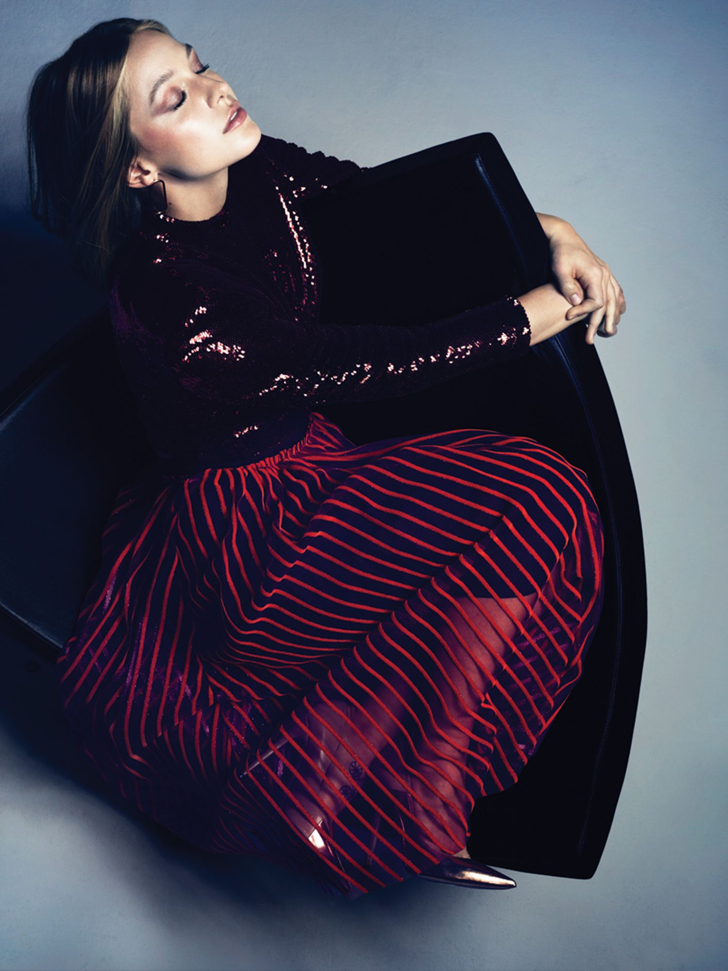 Supergirl's Melissa Benoist sits wearing a shiny dark purple top and red striped velvet skirt.