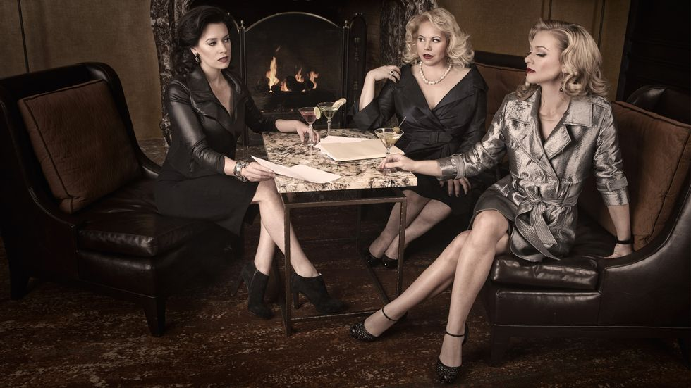 Paget Brewster, Kirsten Vangsness, and A.J. Cook having cocktails next to a fireplace