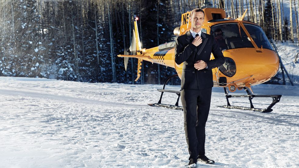 Matthew Gray Gubler on mountain top in a tuxedo with a helicopter