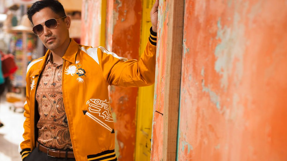 Jay Hernandez of Magnum P.I. wears an orange jacket and sunglasses