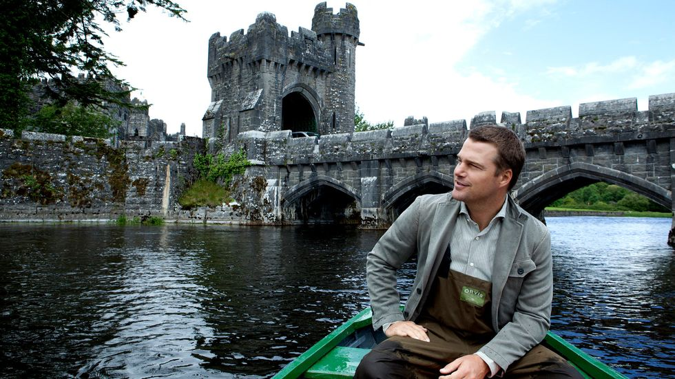 Chris O'Donnell sitting in a green boat on a lake in front of a castle and bridge