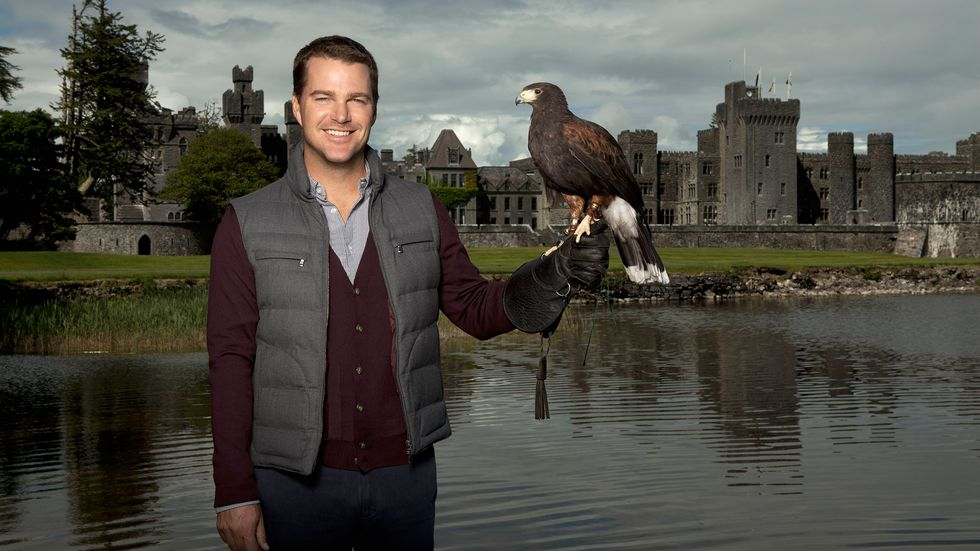 Chris O'Donnell standing in front of a lake and castle holding a hawk