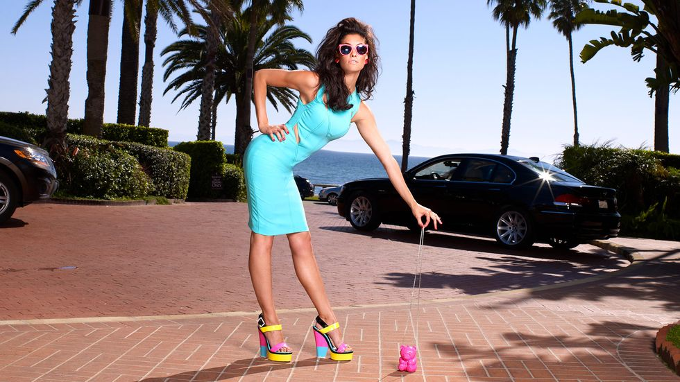 Daniela Ruah in a bright blue dress bending over slightly and holding the chain of a pink bear-shaped purse with two fingers
