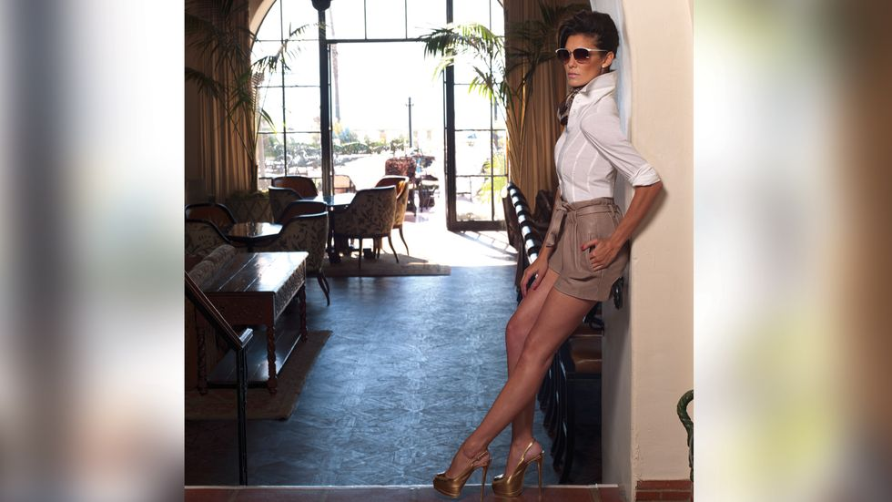 Daniela Ruah in a white button down and camel shorts leaning in an archway
