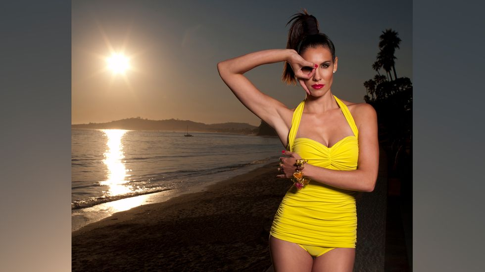 Daniela Ruah in a yellow one piece by the ocean using her fingers to make a hole to look out of
