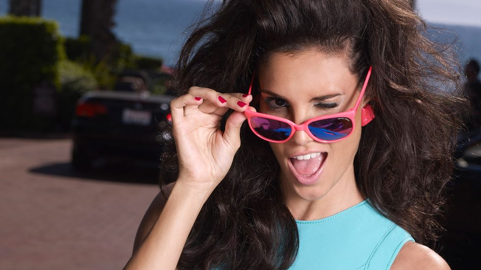 Daniela Ruah playfully winking through a pair of pink sunglasses