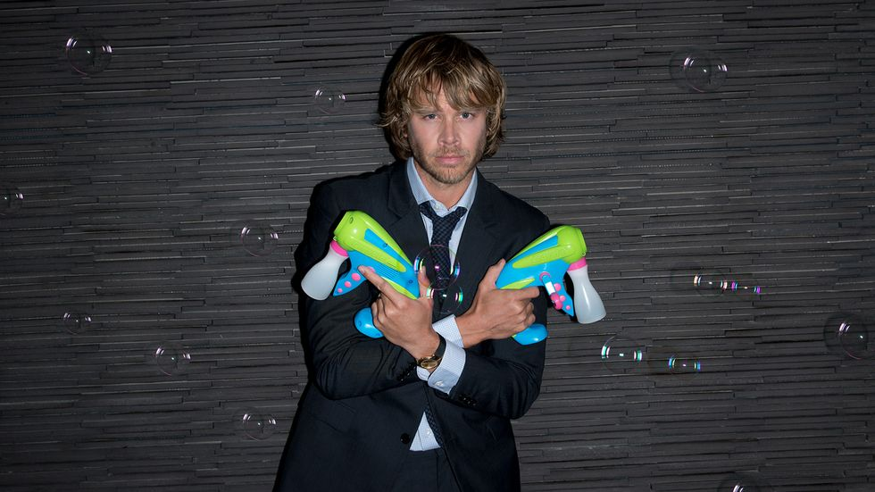 Eric Christian Olsen crossing his arms and holding two bubble guns