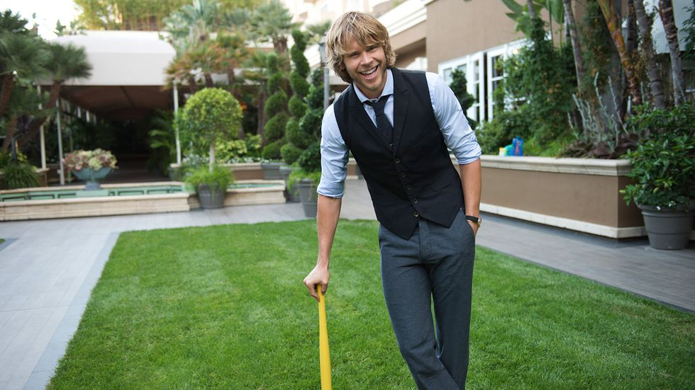 Eric Christian Olsen standing outside in a vest and smiling while leaning on some sports equipment