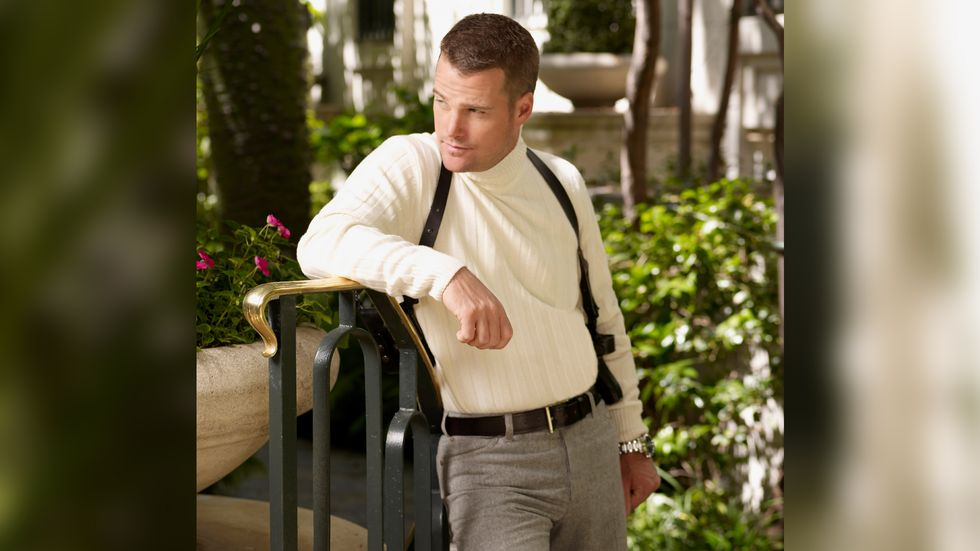 Chris O'Donnell wearing a white turtleneck and leaning on a handrail with a gun holster strapped to his hip