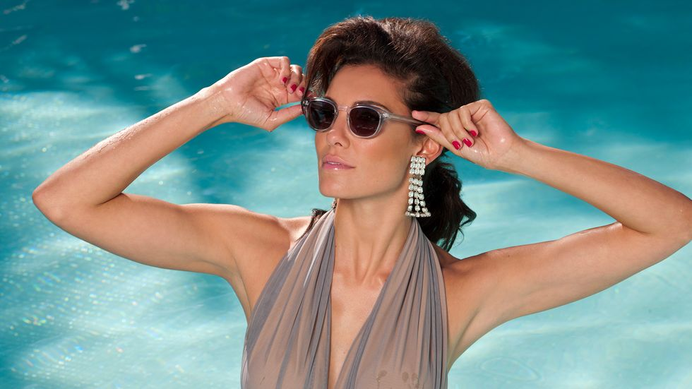 Daniela Ruah in some shades and a halter bathing suit in a pool