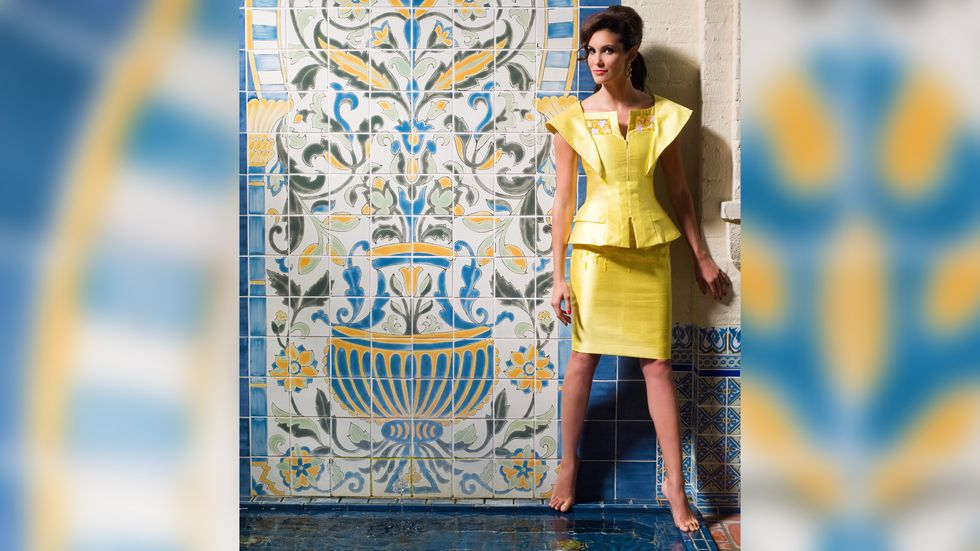 Daniela Ruah in a bold yellow outfit while standing barefoot by an ornate blue and yellow wall