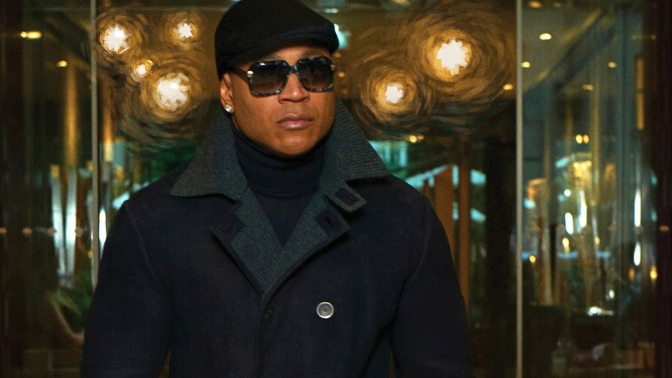 LL COOL J wearing large sunglasses and a black outfit looking stealthy