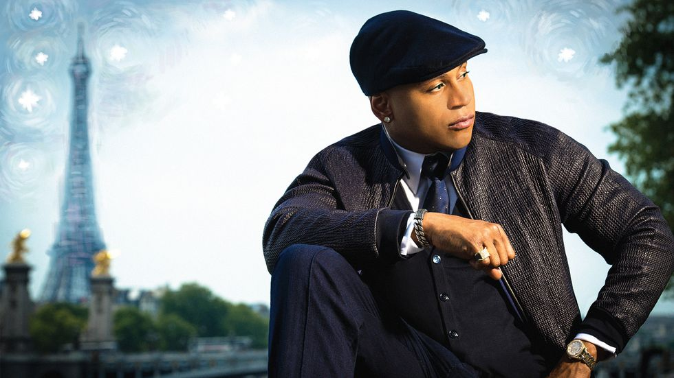 LL COOL J looking off to the side and kneeling in front of a painted background of the Eiffel Tower