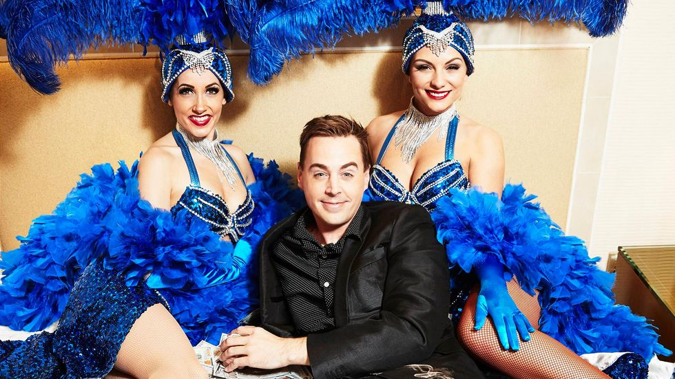 Sean Murray in black outfit with two women in blue