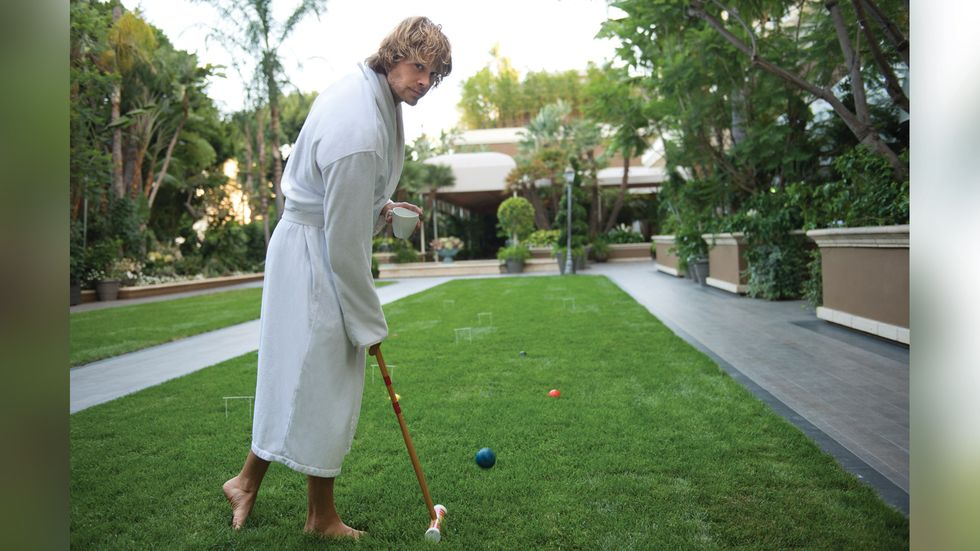 Eric Christian Olsen in a white bathrobe playing croquet outside