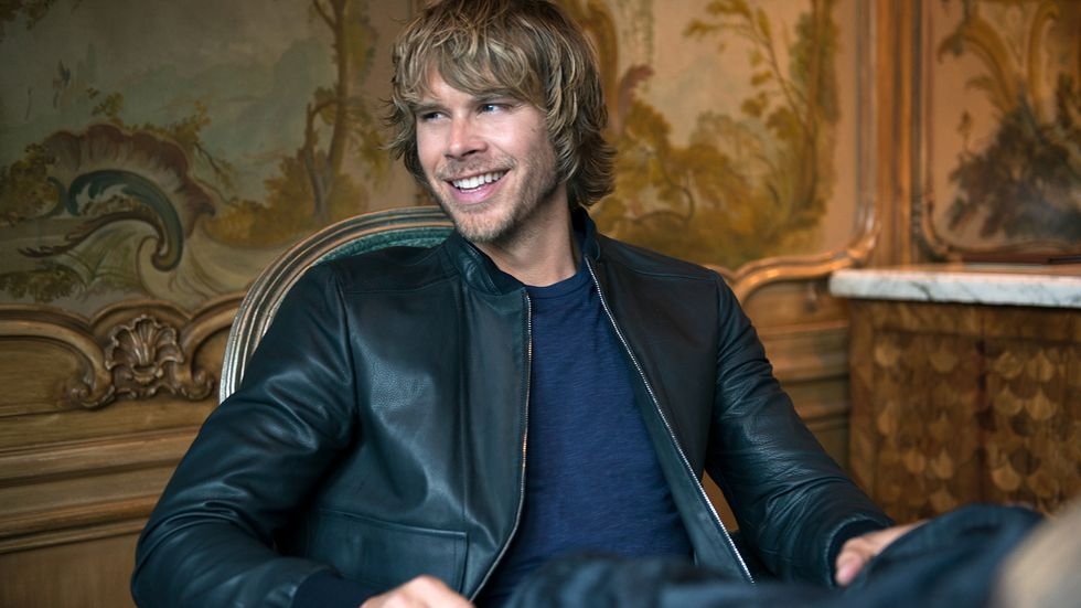 Eric Christian Olsen smiling and looking off in the distance while wearing a leather jacket and sitting down