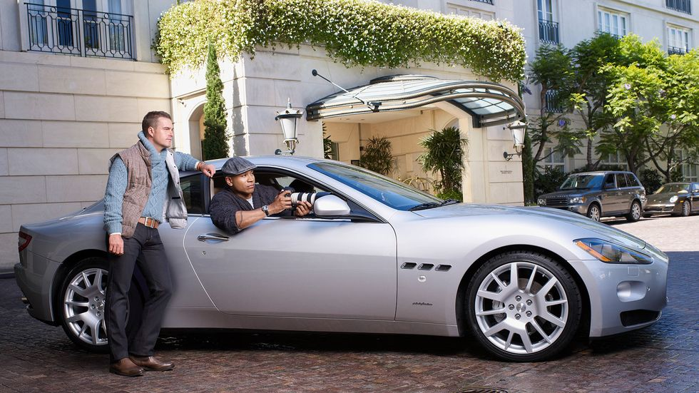LL COOL J sitting in the passenger seat of a silver car while Chris O'Donnell stands outside leaning on the car