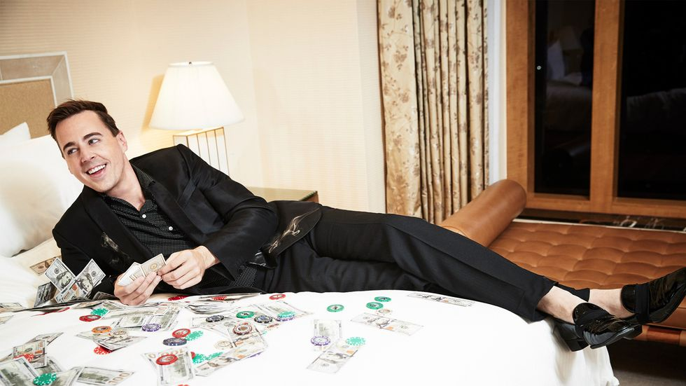 Sean Murray on bed surrounded by money and poker chips