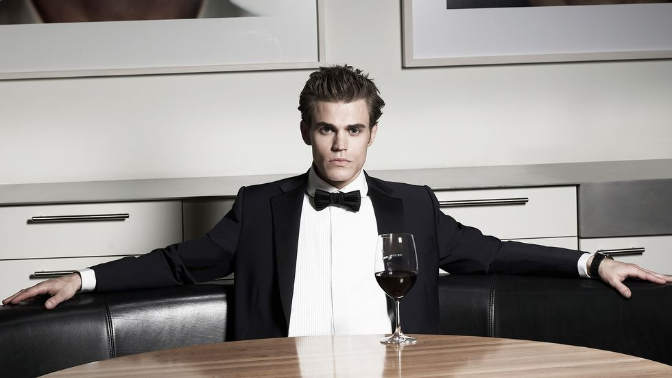 Paul Wesley of Tell Me A Story wears a tuxedo and enjoys red wine