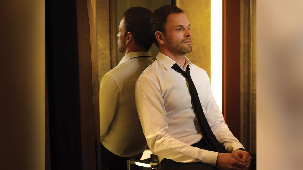 Johnny Lee Miller black tie sitting in front of mirror