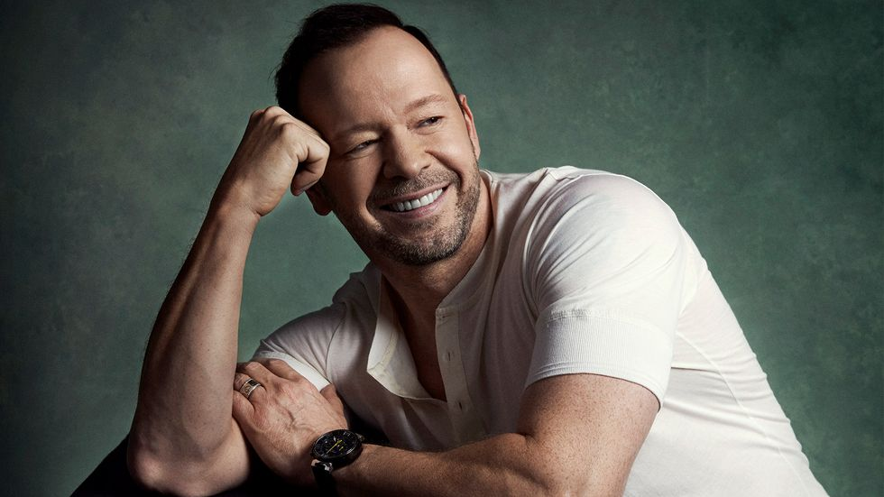 Donnie Wahlberg smiling in white shirt and black watch