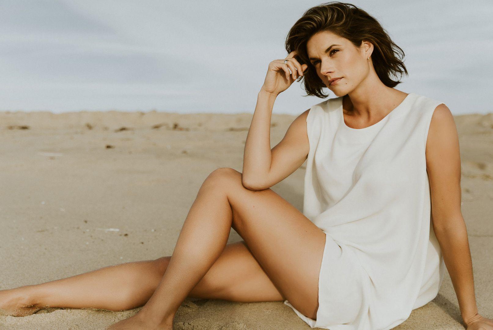 Missy Peregrym sitting on beach sand