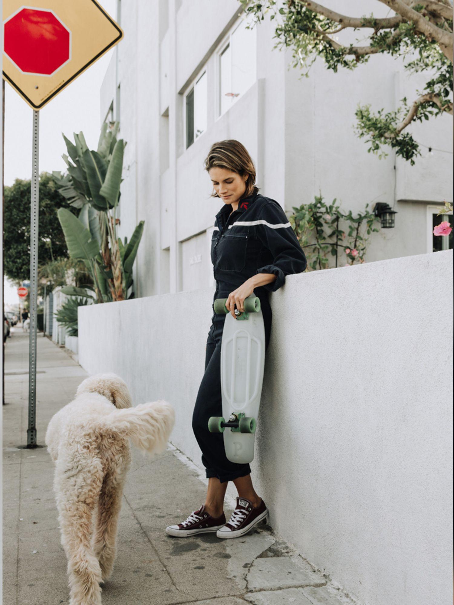 Missy Peregrym with a skateboard and a dog