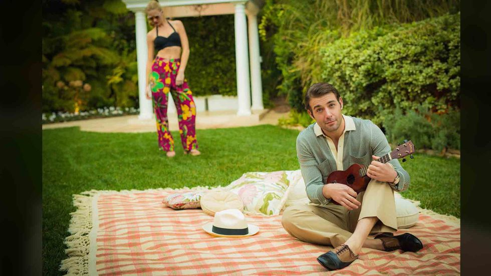 James Wolk sitting on blanket playing ukulele