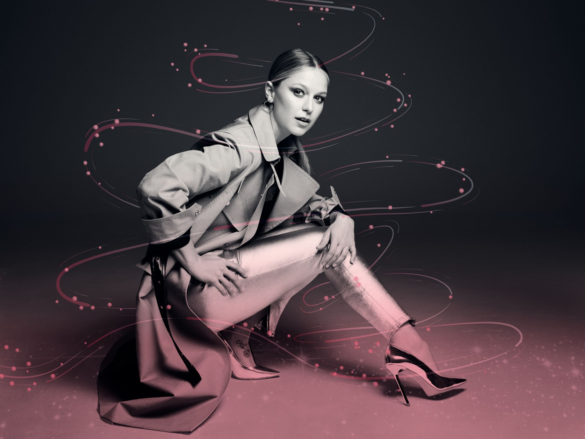 Supergirl Star Melissa Benoist wears a trench coat and shiny pants and shoes.