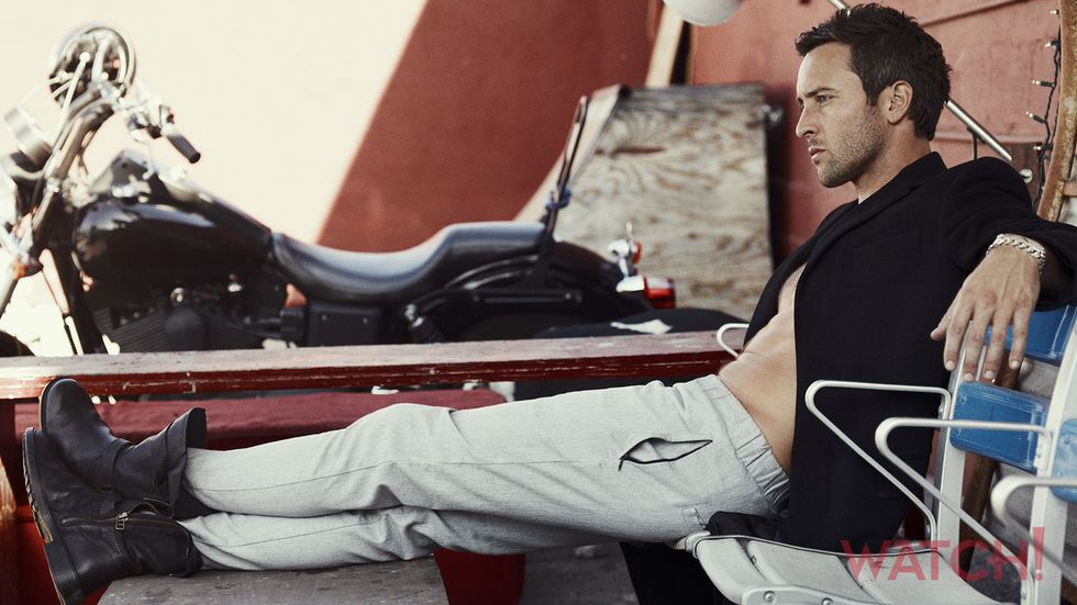 Alex OLoughlin of Hawaii Five 0 next to a motorcycle with his feet up
