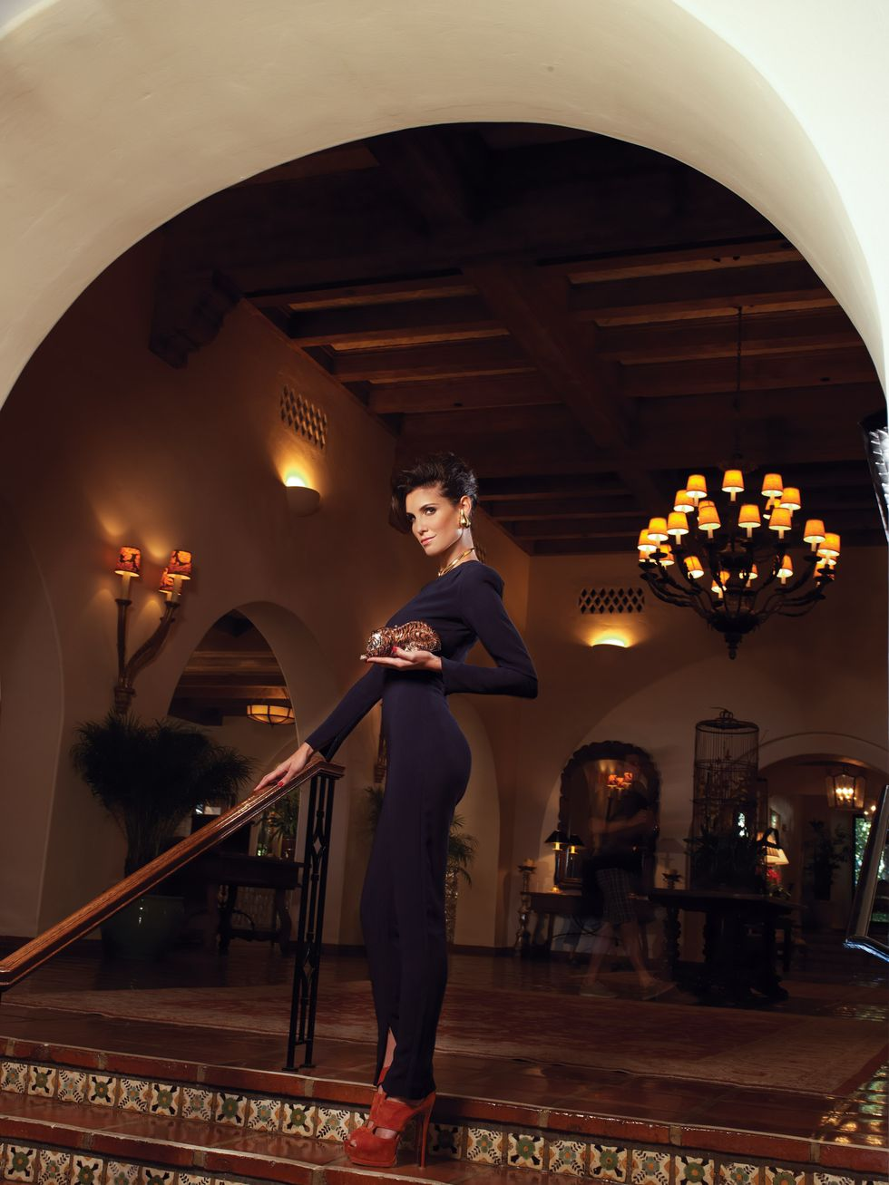 Daniela Ruah wears a tight knit top with black pants while posing at the top of a staircase.
