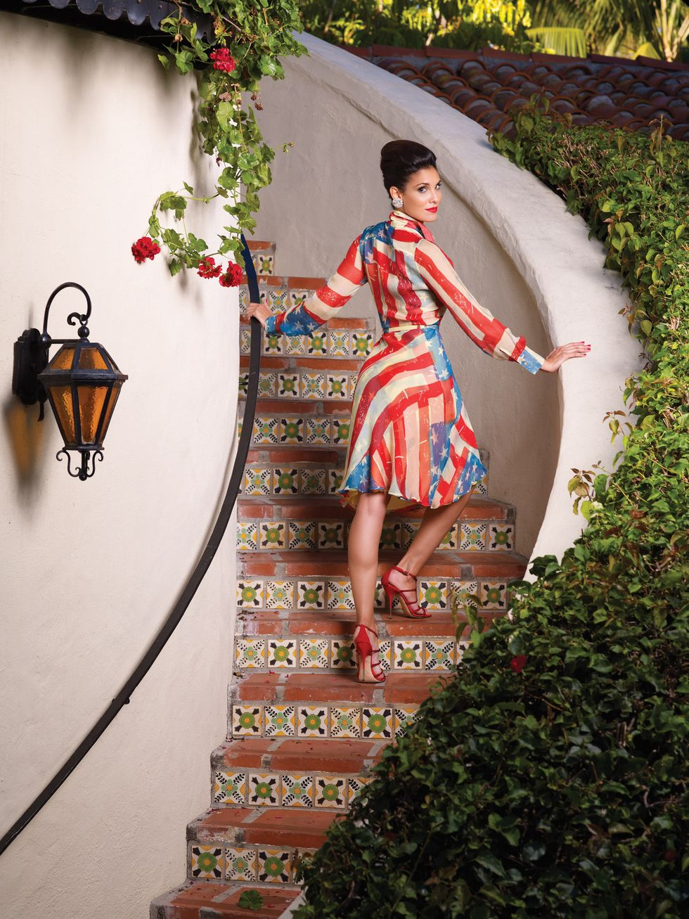 Daniela Ruah climbs a staircase dressed in a loose american flag print dress.