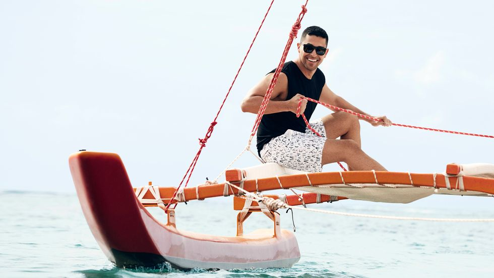 Wilmer Valderrama smiling in a black tank top and white swim trunks sailing on the ocean