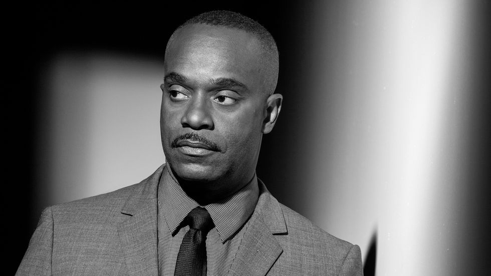 A black and white photo of Rocky Carroll staring off to the left into the distance