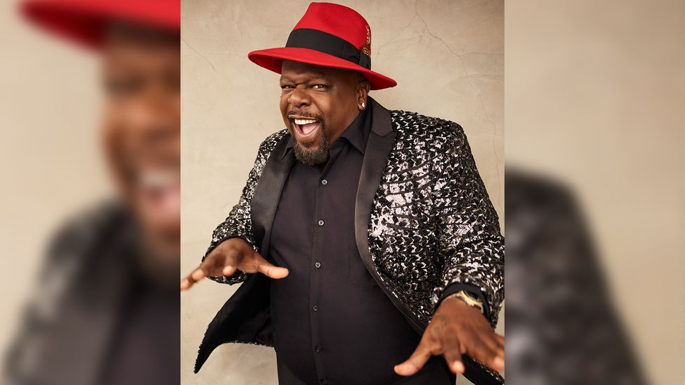 Cedric the Entertainer of The Neighborhood in black sequined jacket and red fedora