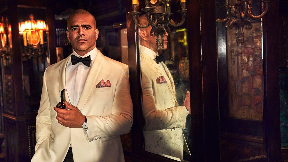 Christopher Jackson of Bull in white tuxedo jacket against mirrored wall