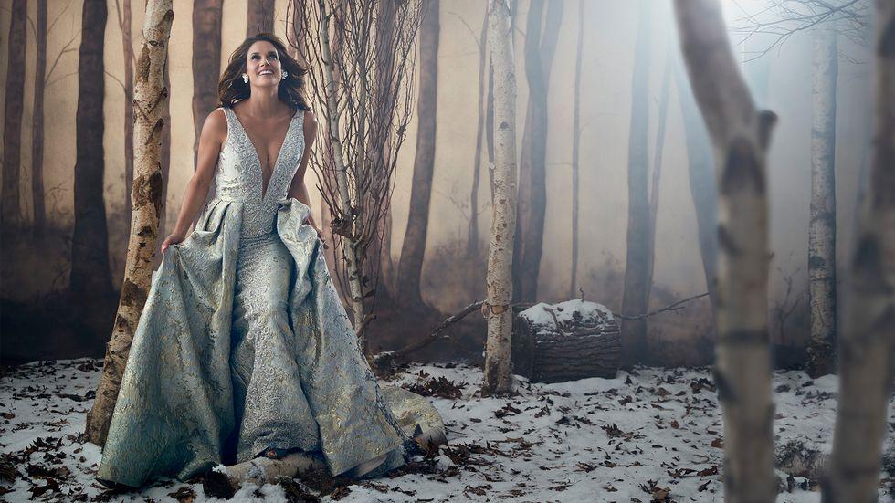 Missy Peregrym of FBI in silver brocade ballgown walking through snowy forest
