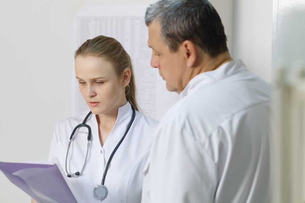 Nurse practitioner consulting with another doctor in a doctor's office.