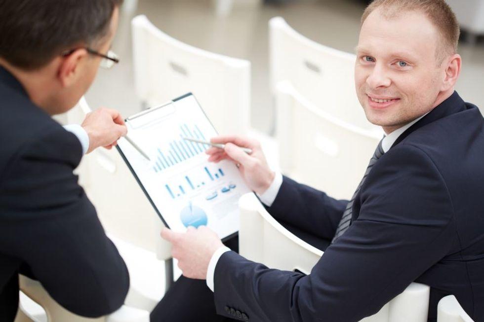 Estatístico revisando dados com um homem de negócios em um escritório.