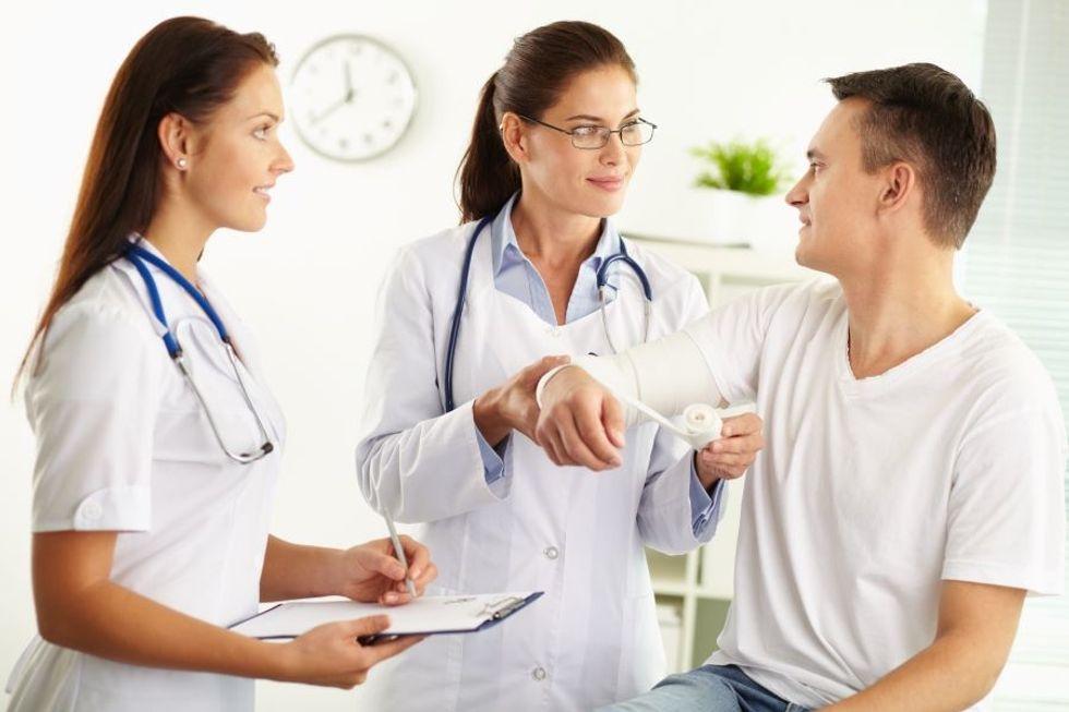 Assistente do fisioterapeuta que ajuda a examinar um paciente no escritório de um fisioterapeuta.