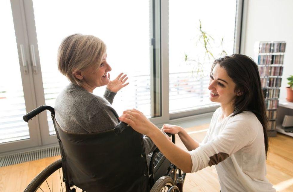 Auxiliar de cuidados pessoais cuidando de um paciente em cadeira de rodas em sua casa.